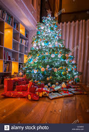 large tree with wrapped gifts presents in home in