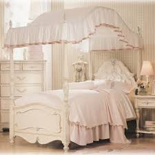 bedroom white bed with thick bedding and high canopy bedframe