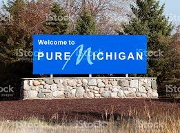 Michigan business travel images Blue welcome to pure michigan sign on a stone wall stock photo