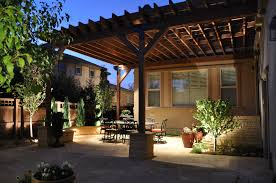tuscan patio and arbor with stone pillars and lighting in