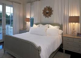 gold sunburst mirror over gray cane bed with footboard french