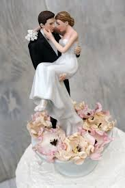 wedding cake tops bed of roses groom holding the wedding cake topper wedding