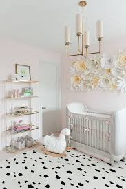 girls nursery with pink walls and large floral wall decor above