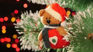 christmas decoration a toy teddy bear on christmas tree bokeh