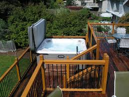 bathroom two level wooden deck with tub and iron round table
