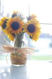 table centerpieces with sunflowers sunflowers in corn kernals with corn husk bow for fall floral
