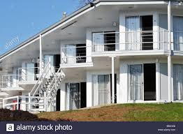 white motel building with balconies stairs and sliding glass
