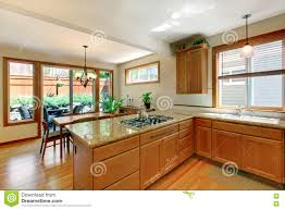 brown and white kitchen room with hardwood floor cabinets and