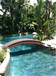 backyard pool landscaping ideas with wooden bridge and tropical