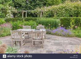 wooden table and chairs in a beautiful ornamental garden stock