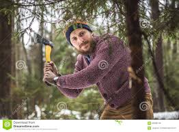 young man is cutting christmas tree in the wood stock photo