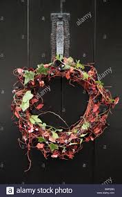 christmas wreath hanging on the front door of an english country