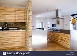 fitted cupboards with walnut veneer doors beside exposed stone