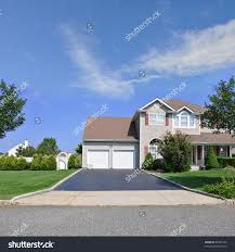 blacktop driveway of split level suburban home with double garage