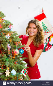 teenage with brown hair decorating a noble fir christmas tree