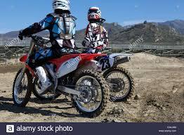 motocross race tracks 2 motocross riders waiting along side race track stock photo