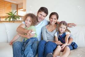 Happy Family Watching TV Together In Their Living Room Stock Photo - Family in living room
