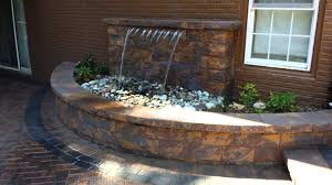 outdoor living space with waterfall and firepit by corad outdoor