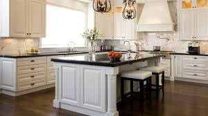 white kitchen island with black granite top cabinets countertops and hardwood floors in the