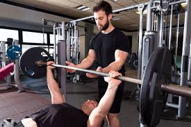 bench press weightlifting man with personal trainer spirit body song