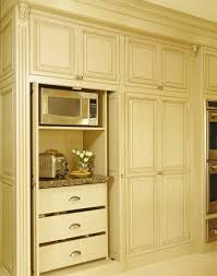 appliance storage built into tall cabinet with pocket doors that