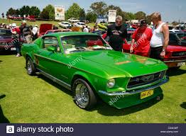 mustang modified car enthusiasts admiring a modified 1967 ford mustang fastback at