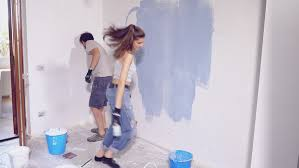 happy couple dancing while painting walls at home slow motion 4k