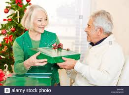senior citizen gifts two happy senior citizens celebrating christmas with gifts stock