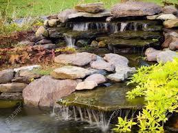 water feature with rocks ornamental plants and flowing