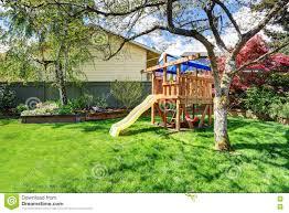view of kids playground in green backyard garden with birch trees