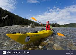 young woman in kayak paddling kayaking clear shallow water of