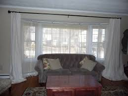 white fabric bay window curtains with black rod and white sheer