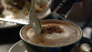 Salep Hd sugar in motion falling in a cup of coffee on a table