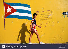 colors close to yellow cuba havana young woman w american flag suit walking close to