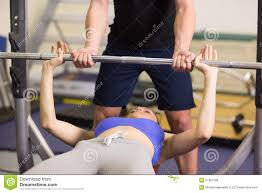 Lift Bench Trainer Helping Woman To Lift The Barbell Bench Press In Gym Stock