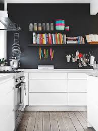 un mur noir avec une cuisine blanche agencée en l kitchens