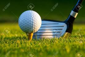 golf ball on tee in front of driver on a gold course stock photo