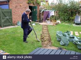 man digging out turf for new garden path in modern british house