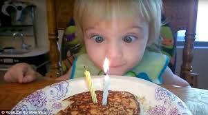 boy tries and fails to blow out his birthday cake candles with his