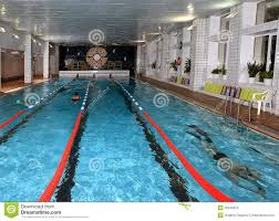 interior public indoor swimming pool with vacationers people