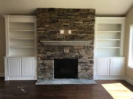 stacked stone fireplace with a flagstone mantle and custom built