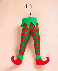 santa and elf legs stuck in the christmas tree decor the green