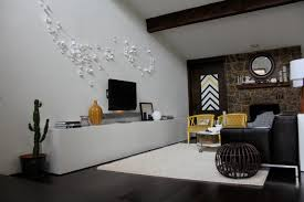 white living room wall with brown stone fireplace and white wooden