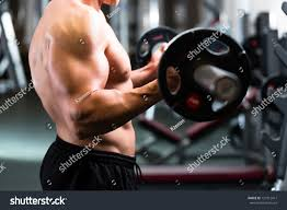 strong man bodybuilder dumbbells gym exercising stock photo