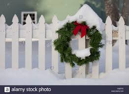Snow At Home by Christmas Wreath On White Picket Fence Covered With Snow At The