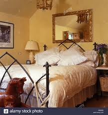 gilt mirror above gothic style wrought iron bed with white duvet