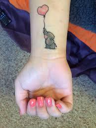baby elephant with heart shape balloon tattoo on wrist
