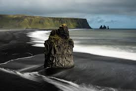 a basalt sea stack on a black sand beach in iceland 16001068