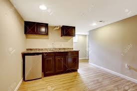 empty basement room with dark brown kitchen cabinets mother in