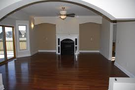 brown wooden floor connected by white fireplace and beige white